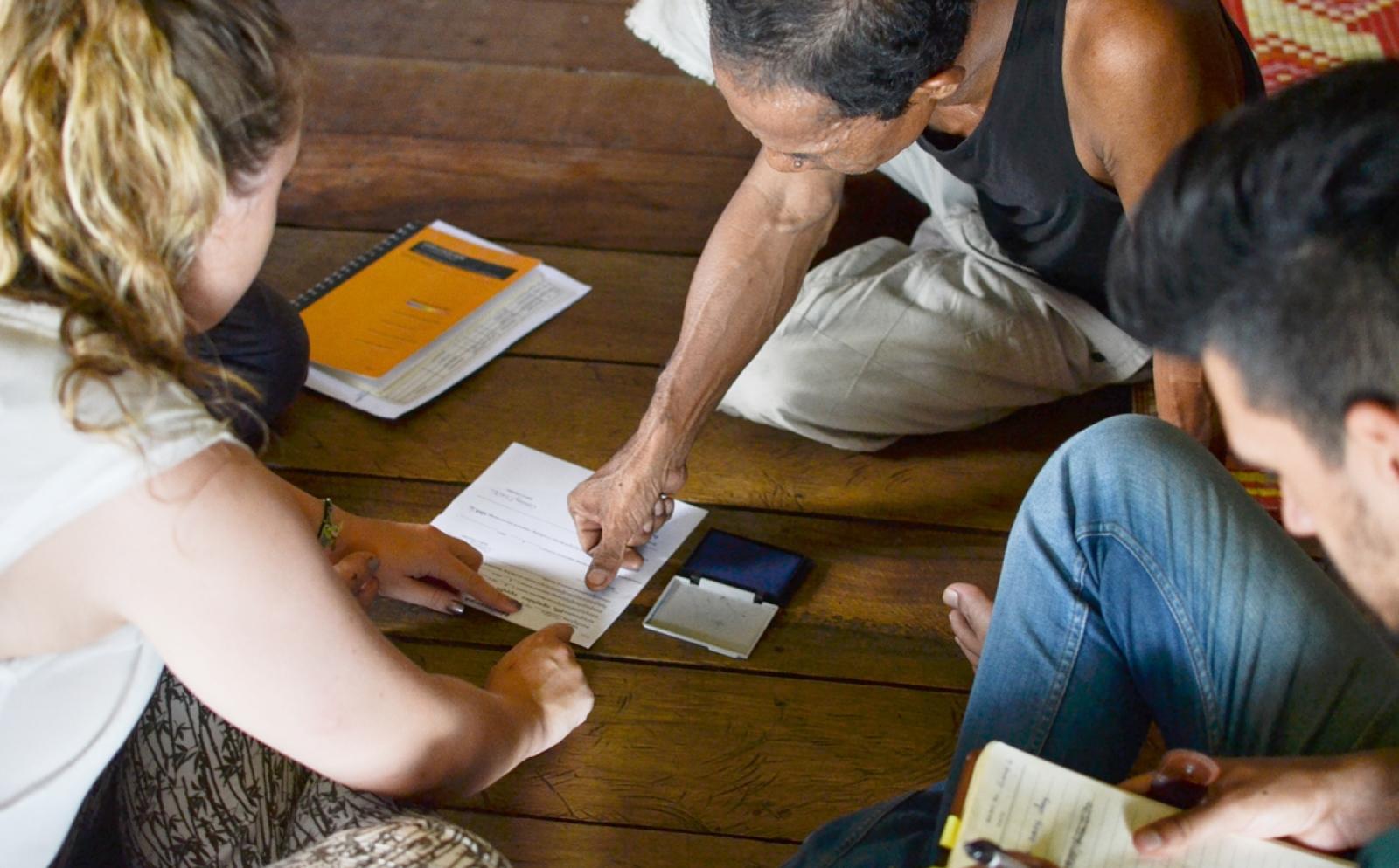 カンボジアのローン受益者の契約をアシストするマイクロファイナンスインターン